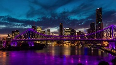 Night time panorama of Brisbane city with purple lights on Story Bridge Stock Footage