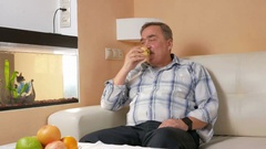 Man aged mustache resting at home and eats an apple. He looks at fish in an Stock Footage