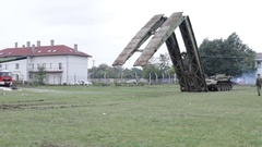 Armoured vehicle-launched bridge, lowering the bridge to the ground in front Stock Footage