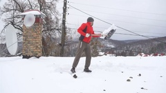 Slow Motion Man with a shovel removing snow from a roof. Caucasian men using Stock Footage