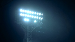 Rack focus of stadium lights in front of a dark blue sky Stock Footage
