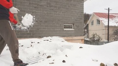 Man with a shovel removing snow from a roof. Caucasian men using to shovel he Stock Footage