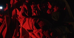 Pan up from ground to two firemen, bathed in red emergency light. Stock Footage