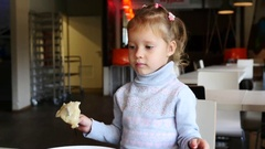 Little kid girl portrait eating with fork in a food court restaurant Stock Footage
