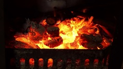 Fire and embers behind bars in the furnace of a metal chimney. Stock Footage