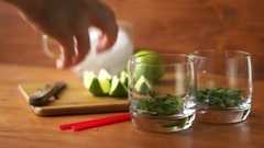 Person presses sliced lime in a glass for a a mojito cocktail.. Stock Footage