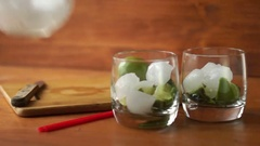 A person puts a spoon ice in glasses with lime and mint for a mojito cocktail Stock Footage