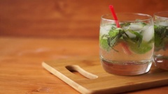 A glass of mojito cocktail with lime, mint and ice, shooting from left to right. Stock Footage