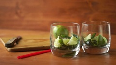 A person puts a spoon ice in glasses with lime and mint  for a mojito cocktail. Stock Footage