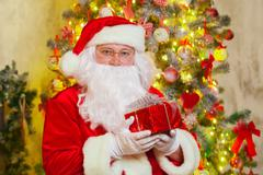 Santa Claus with giftbox on background of sparkling firtree Stock Photos