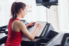 Sports woman is running on the treadmill Stock Photos