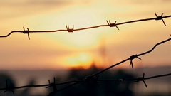 Barbed wire prison sunset orange Stock Footage