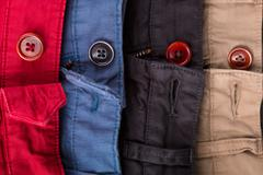 Fragment of four cotton twill pants red, blue, black, beige with open buttons Stock Photos