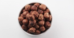 Organic hazelnuts in bowl on white background loopable rotation video Stock Footage
