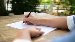 Selective close up at hand of woman writing on the white paper by pencil. Stock Footage