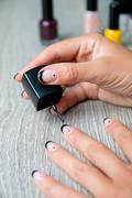 Black nail polish being applied to hand with tools for manicure on background Stock Photos