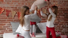 Triplets sisters dressed in xmas pajamas are having a pillow fight on the bed Stock Footage