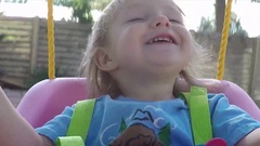 Slow Motion Two Year Old Girl Smiling On Swing Stock Footage