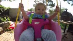 Little Girl having fun on Toddler Rope Swing Stock Footage