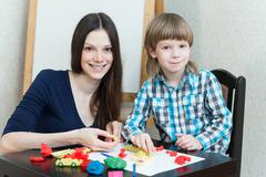 Child kid boy and mother play colorful clay Stock Photos