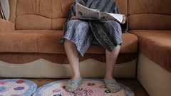 The man in a bathrobe and knitted sneakers sitting on couch and reading journal. Stock Footage