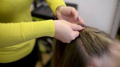Hairdresser plaiting braids for girls brunette Stock Footage