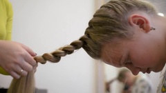 Hairdresser plaiting braids for girls brunette Stock Footage