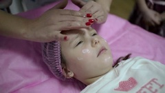 Beautician Hands Stroking The Face Of The Client. Facial Massage for Child Girl Stock Footage