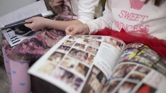 Two Girls Reading Through A Glossy Magazine Fashion Clothing Catalog Stock Footage