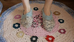 Men's feet in knitted slippers socks stamp on the spliced rug. Close up. Stock Footage