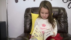 Little Girl Reading Through A Glossy Magazine Fashion Clothing Catalog Stock Footage