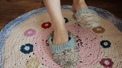 The man puts his feet on the floor and clothes the knitted slippers socks. Stock Footage