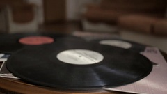 The man puts vintage gramophone record on the table with other records. Stock Footage