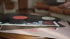 Male hands take the vinyl record from the table to listen the music. Close up. Stock Footage