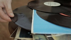 Male hand pulls old and used vinyl record out of its cover in the LP stack. Stock Footage