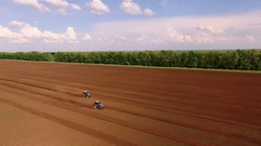 Bird view two tractor on ploughed field 3 Stock Footage