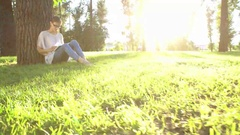 Woman Reading Book By The Tree In Park Stock Footage
