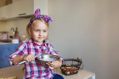 Portrait of pretty little girl in checkered shirt whips up a cream on a kitch Stock Photos