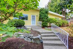 House exterior with yellow clapboard siding and concrete porch with stairs. N Stock Photos