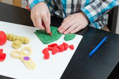 Boy sculpts from plasticine at home Stock Photos