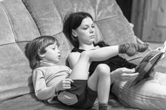 Mother and her son read book Stock Photos