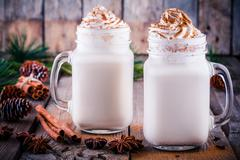 Christmas drink: eggnog with whipped cream and cinnamon in mason jars Stock Photos