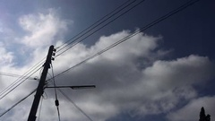 Time lapse clouds with electric pole standing with trees Arkistovideo