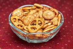 Salty snacks in glass bowl Stock Photos