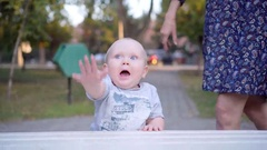 Little baby boy learns to walk along the bench. In the park. Outdoor Stock Footage
