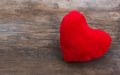 Old textured background of cracked barn boards and the red plush heart Stock Photos