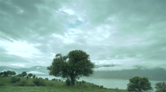 Dark clouds move fast over a lake and green meadow Stock Footage