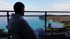 Sitting with his back to the man on the balcony with sea views Stock Footage