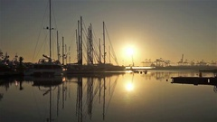 Sunrise in the harbor of Valencia, the sun rises between docked sailboats and Stock Footage