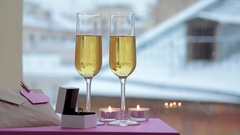 Two glasses of champagne, ring in box and note with heart in winter Stock Footage